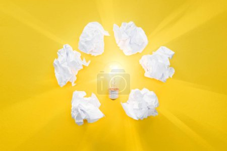top view of glowing light bulb in circle of crumbled paper balls on yellow background, having new ideas concept