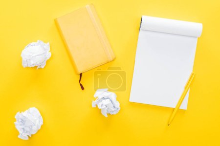 blank notebook and crumbled paper balls on yellow background