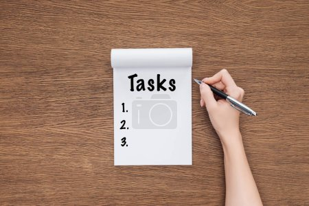cropped view of woman writing word 'tasks' in notebook on wooden background