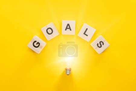 top view of glowing light bulb under 'goals' word made of wooden blocks on yellow background, goal setting concept