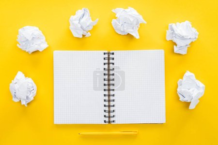 blank spiral notebook and crumbled paper balls on yellow background