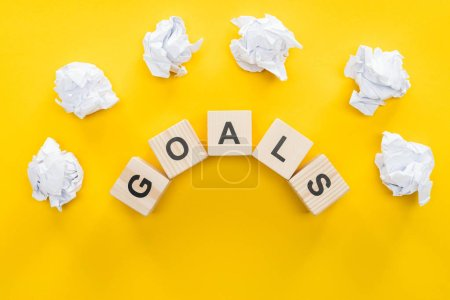 Photo pour Boules de papier émietté sur le mot «objectifs» consistant de blocs en bois sur fond jaune, notion de paramètre objectif - image libre de droit