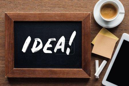 """Kreidetafel von oben mit """"Idee"""" -Schriftzug mit Kaffee und digitalem Tablet auf Holzgrund"""