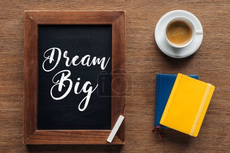 Photo for Top view of chalk board with 'dream big' lettering on wooden background - Royalty Free Image