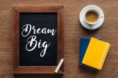 top view of chalk board with 'dream big' lettering on wooden background