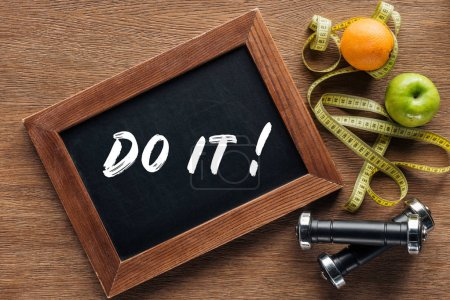 fruits, dumbbells, measuring tape and wooden chalk board with 'do it' quote, dieting and healthy lifesyle concept