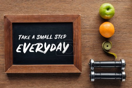 fruits, dumbbells, measuring tape and wooden chalk board with 'take a small step everyday' quote, dieting and healthy lifesyle concept
