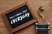 measuring tape, dumbbells and wooden chalk board with 'take a small step everyday' quote, dieting and healthy lifesyle concept