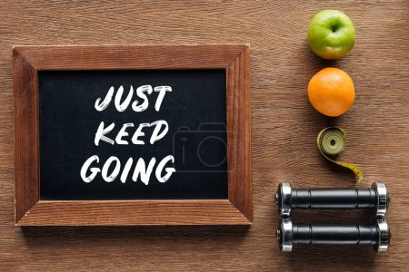 fruits, dumbbells, measuring tape and wooden chalk board with 'just keep going' quote, dieting and healthy lifesyle concept