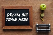 apple, dumbbells, measuring tape and wooden chalk board with 'dream big train hard' quote, dieting and healthy lifesyle concept
