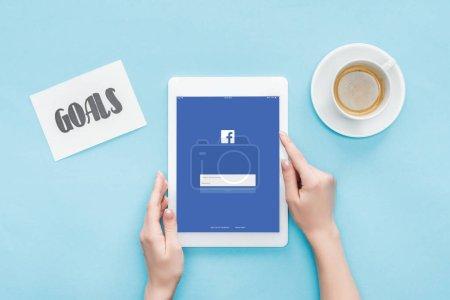 Ausgeschnittene Ansicht von Frauen mit digitalem Tablet mit Facebook-App auf dem Bildschirm, Zielbuchstaben auf Karte und Kaffee auf blauem Hintergrund