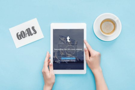 cropped view of female using digital tablet with tumblr app on screen, goals lettering on card and coffee on blue background