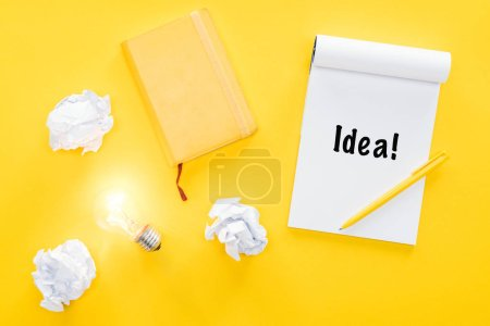 notebook with 'idea' word, crumbled paper balls and glowing light bulb, having new ideas concept