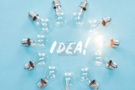 circle of light bulbs with glowing one surronding 'idea' word, having new ideas concept