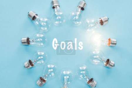 circle of light bulbs with glowing one surronding 'goals' word on blue, goal setting concept