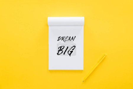 Photo for Top view of notebook with 'dream big' quote on yellow, goal setting concept - Royalty Free Image