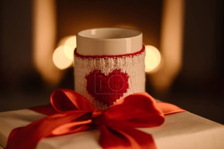 present and knitted mug with heart symbol on blurred background