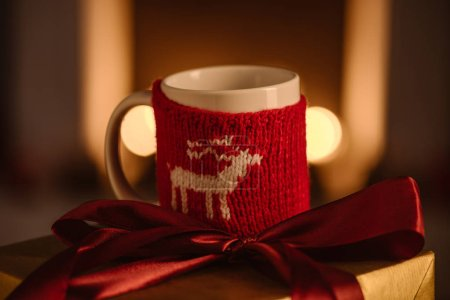 present and festive knitted mug with deer on blurred background