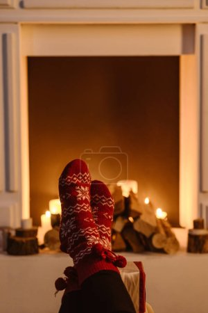 cropped view of woman in festive winter socks with fireplace on background