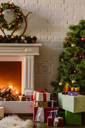 Foto de Árbol de Navidad con decoraciones festivas y cajas de regalo junto a la chimenea con leña en sala de estar - Imagen libre de derechos