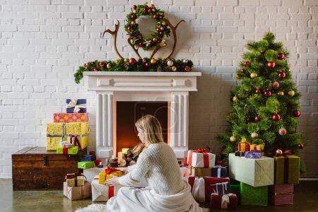 junge Frau in Decke gehüllt legt Geschenke neben Kamin mit Brennholz zu Hause