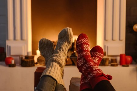 Photo for Cropped view of women wearing winter socks with fireplace on background - Royalty Free Image