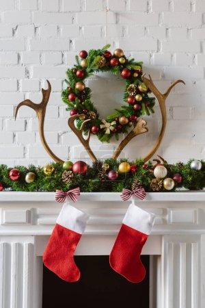 Foto de Festiva guirnalda de la Navidad con adornos, las medias y los ciervos de cuernos sobre la chimenea de la chimenea - Imagen libre de derechos