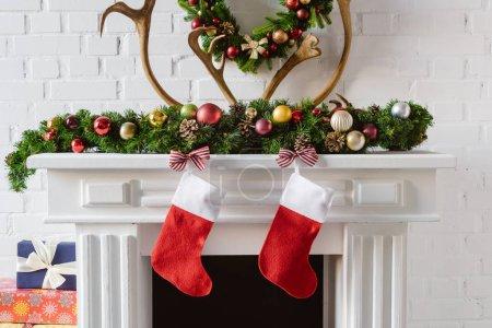 Foto de Corona de Navidad con adornos, las medias y los ciervos de cuernos sobre la chimenea de la chimenea - Imagen libre de derechos