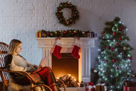 young woman on wicker rocking chair using laptop in living room decorated for christmas