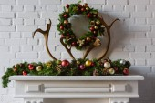 christmas wreath with decorations and deer horns over fireplace mantel