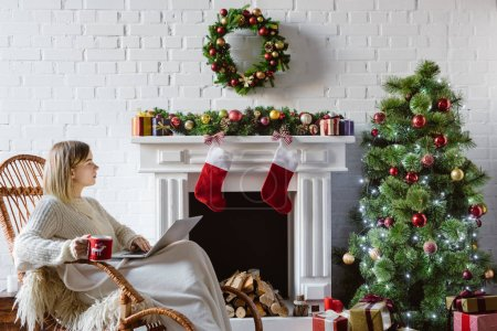 Photo for Beautiful young woman on wicker rocking chair holding coffee cup and using laptop in living room decorated for christmas - Royalty Free Image