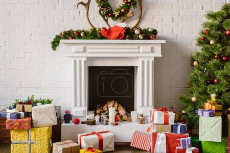 festive decorations over fireplace with gift boxes and christmas tree
