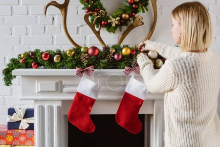 young woman adjusting christmas baubles at fireplace
