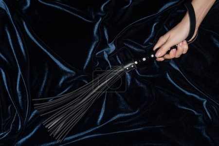 close up of of female hand holding flogging whip with dark velvet cloth at background
