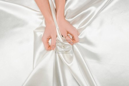 cropped view of female hands tightly holding shiny satin cloth
