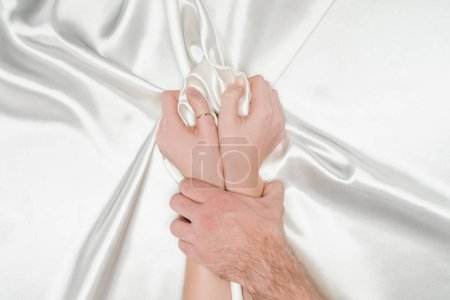 male hand tightly holding female hands on silk white cloth