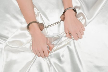 partial view of female hands in handcuffs holding shiny white satin cloth