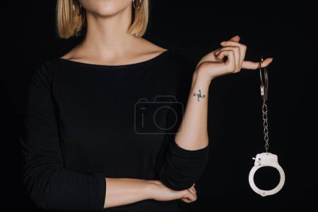 cropped view of blonde woman holding shiny handcuffs isolated on black