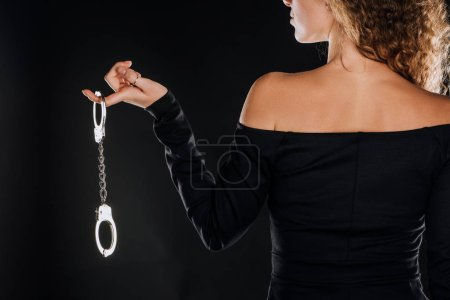 back view of curly woman holding silver handcuffs isolated on black