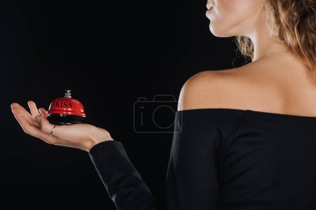 Photo for Cropped view of woman holding red service bell isolated on black - Royalty Free Image