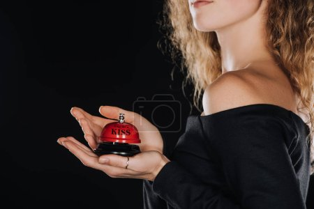 "Photo for Partial view of woman holding red service bell with ""ring for a kiss"" lettering isolated on black - Royalty Free Image"