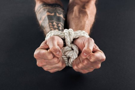 cropped view of male hands bound with rope isolated on black