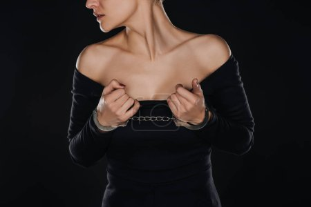 cropped view of woman with open shoulders in handcuffs isolated on black