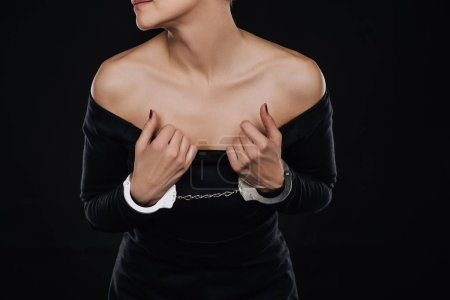 partial view of adult woman in silver shiny handcuffs isolated on black