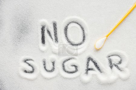 "top view of ""no sugar"" lettering written on granulated sugar with plastic spoon"