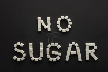 """top view of """"no sugar"""" lettering made of sugar cubes isolated on black"""