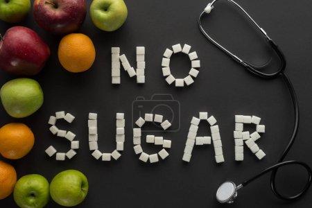 Photo pour Vue de dessus du membre de phrase «sans sucre» faite de morceaux de sucre avec stéthoscope et fruits sur fond noir - image libre de droit