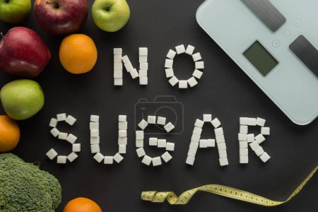 """top view of """"no sugar"""" phrase made of cubes among fruits with scales on black"""