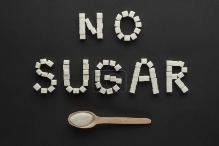 """flat lay of """"no sugar"""" lettering made of cubes with wooden spoon isolated on black"""