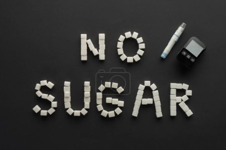 """no sugar"" lettering made of cubes with medical equipment on black"